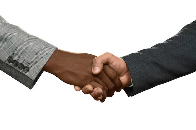 Два бизнесмена пожимают друг другу руки. теперь мы партнеры. знай своего врага. честность или обман.