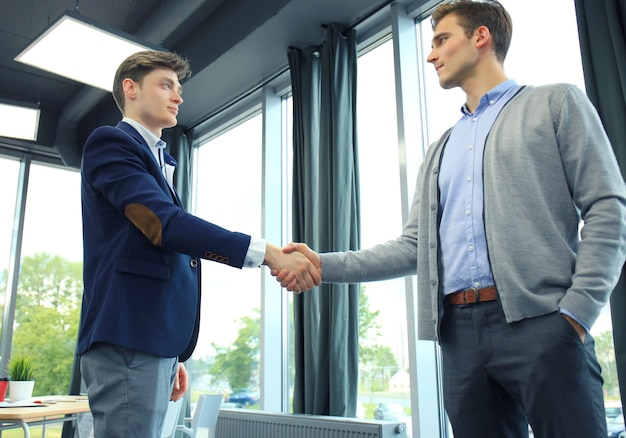 Two businessman shaking hands. welcome to business.