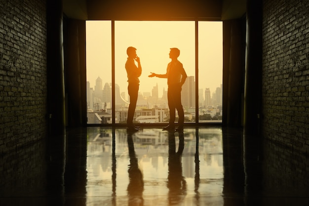 Two businessmen are negotiating business in office on the building.