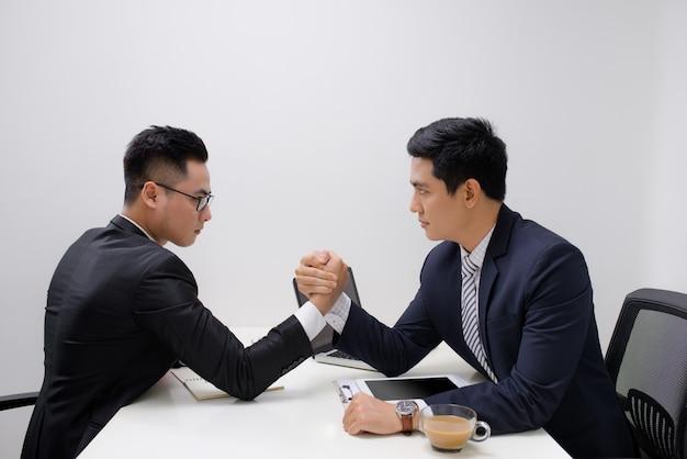 Два бизнесмена соревнуются в армрестлинге в офисе
