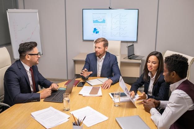 2人のビジネスマンがスピーチポイントについて相談し、2人の異文化間の同僚が論文について話し合っている