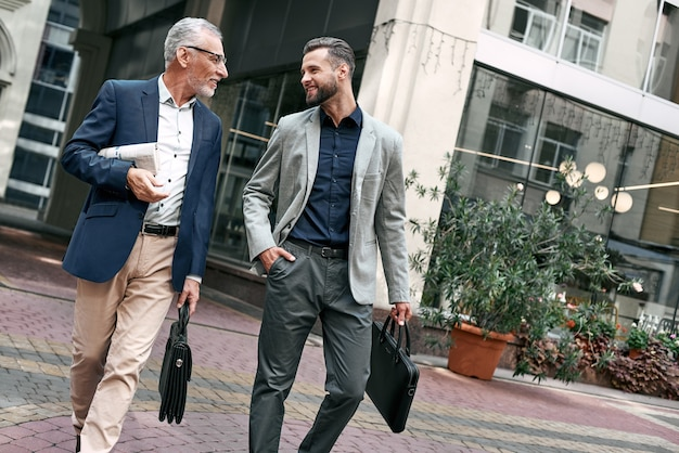 Two businessmen discussing about the new project while walking outdoors