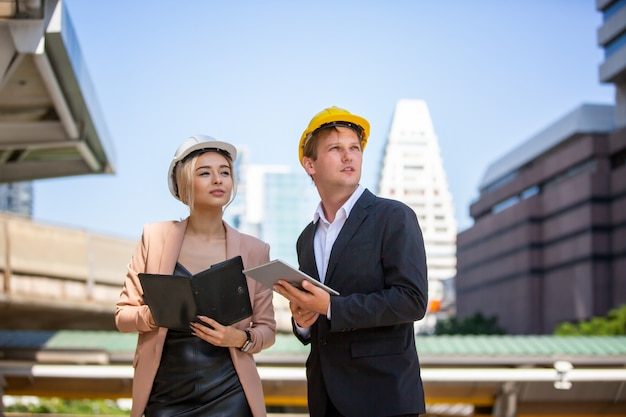 Two businessmen and female wearing safety vests talking and handshake on construction site