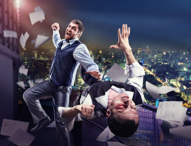 Two businessmen fighting on the roof against night cityscape