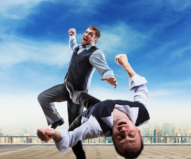 Two businessmen fighting on the roof