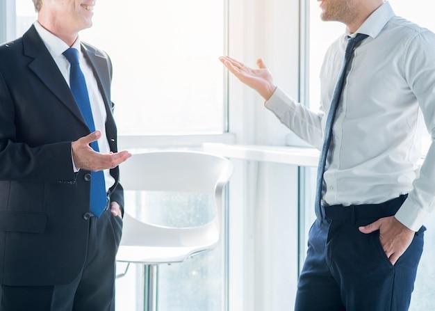 オフィスで会話しながら身に着けている2人のビジネスマン