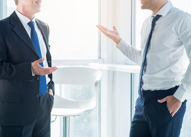 Two businessmen gesturing while having conversation in office