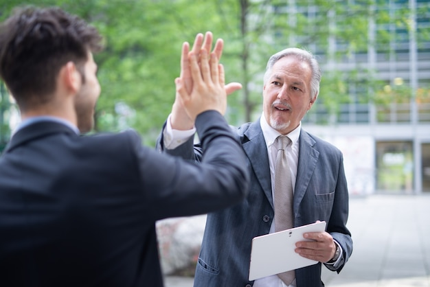 Two businessmen giving each other a high five, business people success concept