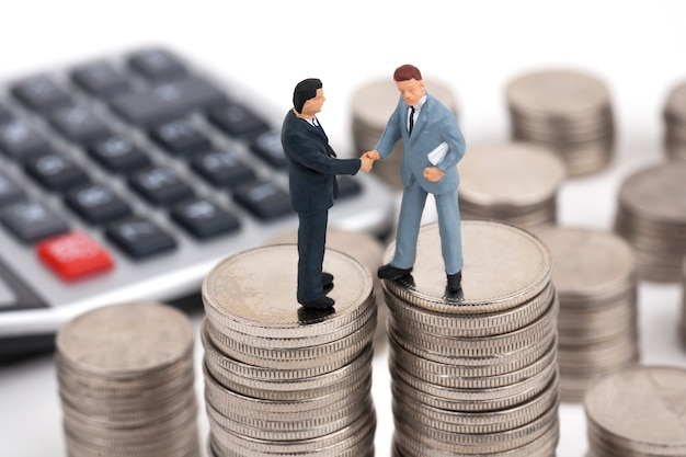 Two businessmen handshake on top of stack of coins
