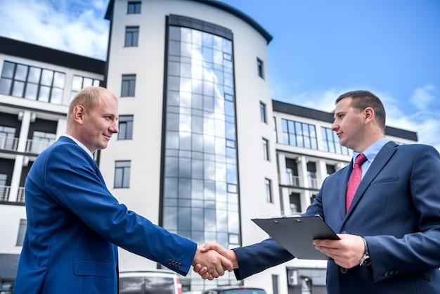 Рукопожатие двух бизнесменов против нового здания
