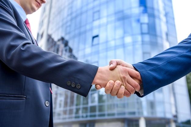 屋外の新しい建物の前に握手する2人のビジネスマン