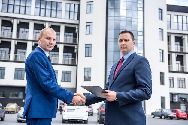 屋外の高層ビルの近くで握手する2人のビジネスマン