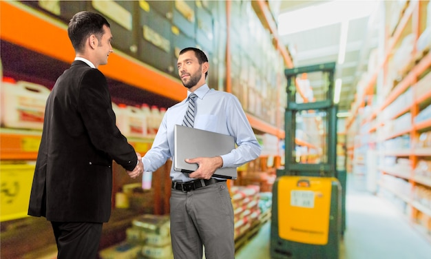 Two businessmen handshaking while holding laptop at warehouse