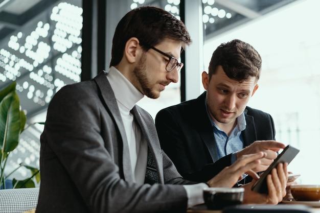 スマートフォンを使って会話する2人のビジネスマン