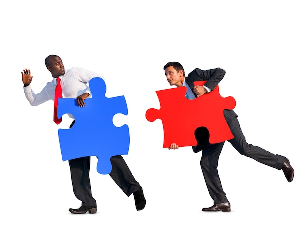 Two businessmen holding jigsaw puzzles in a white background