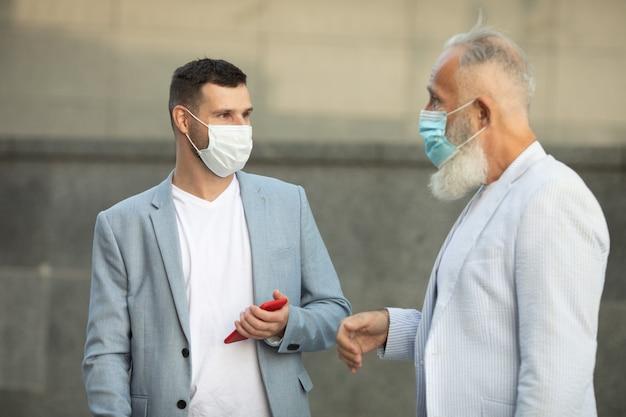 オフィスビルの外で話し合う保護マスクの2人のビジネスマン