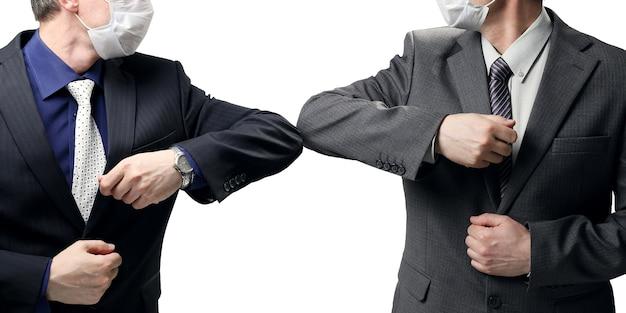 スーツを着た2人のビジネスマンが感染の危険性のため握手なしでお互いに挨拶します
