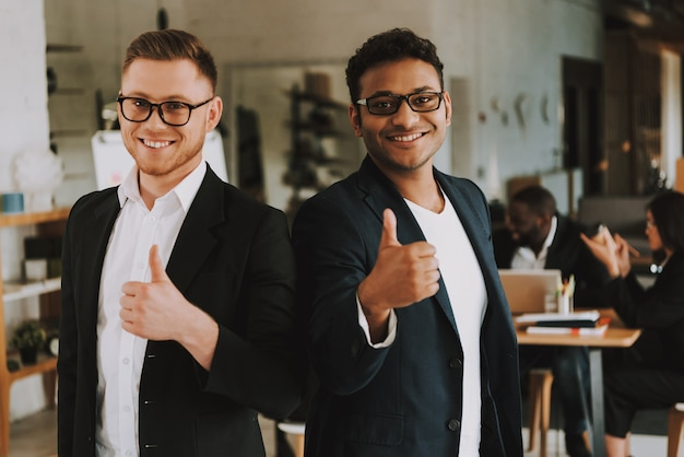 Two businessmen is showing thumbs up and smiling.