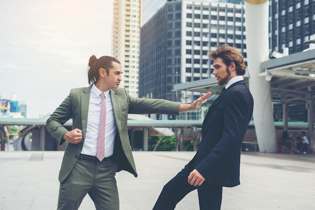 Two businessmen mad each other  trying to come to an agreement.