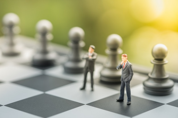 Two businessmen miniature mini people figures standing on chessboard with chess pieces.