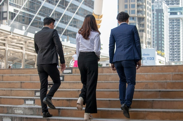 Two businessmen and one business woman are pacing the stairs steps in the city