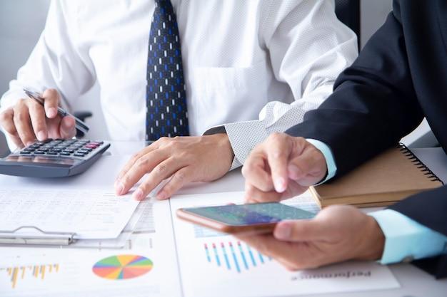 Два бизнесмена или аналитика в конференц-зале анализируют эффективность бизнеса