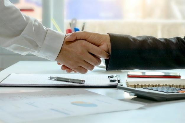 Два бизнесмена обмениваются рукопожатием после окончания соглашения о сотрудничестве в коллективе.