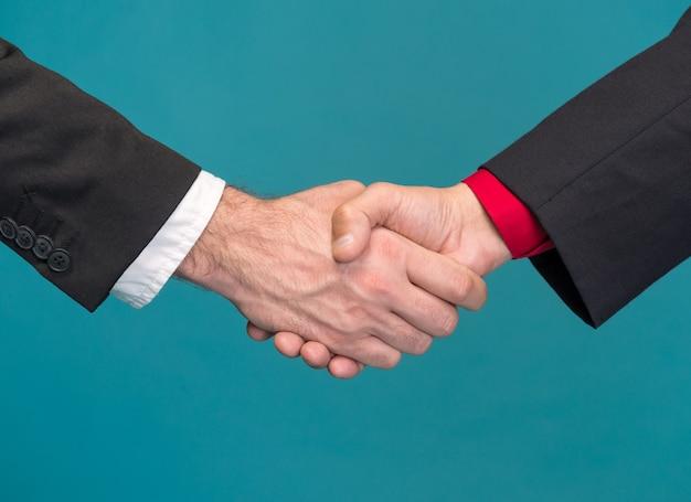 Два бизнесмена, пожимая руки на синем фоне