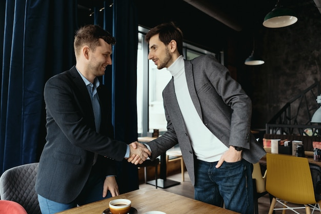 Due uomini d'affari si stringono la mano mentre si incontrano nella hall
