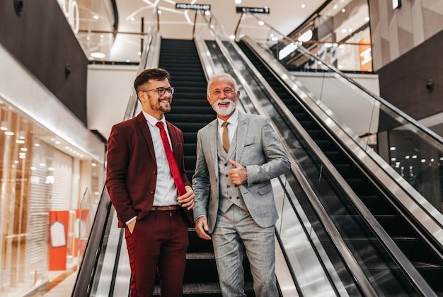 エスカレーターの前に立って話している2人のビジネスマン。