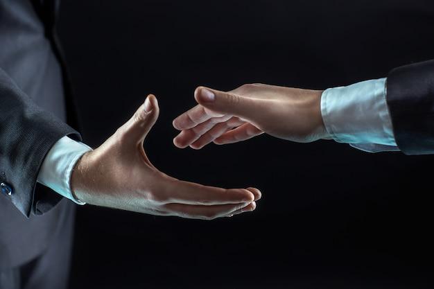 2人のビジネスマンが握手を求めて手を前に伸ばします