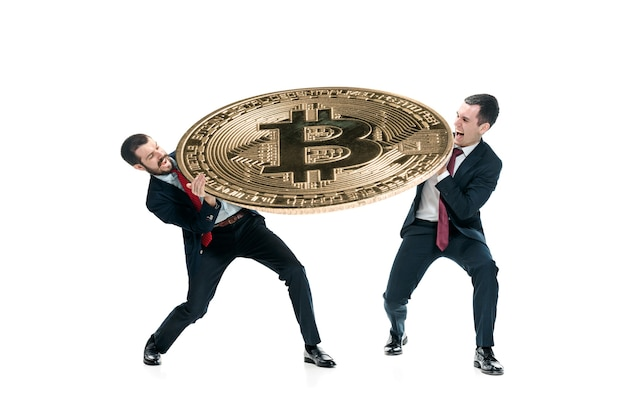 Two businessmen in suits holding business icon - big bitcoin isolated on white background. crypto-currency coins, litecoin, ethereum, e-commerce, finance concept. collage