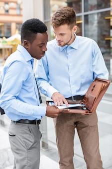 Два бизнесмена говорят и смотрят на документы