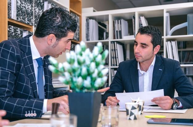 本社のテーブルに座って会議で話している2人のビジネスマン