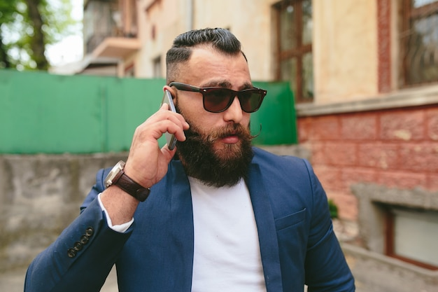 Two businessmen talking on the phone in the city