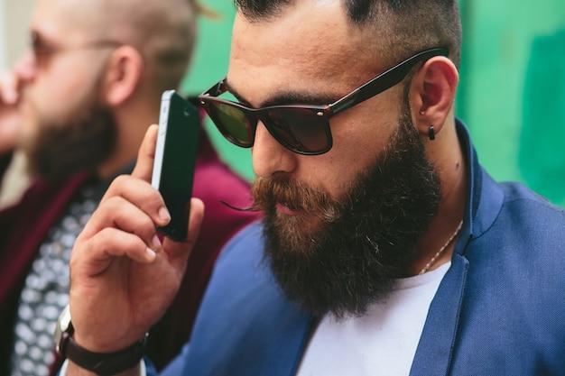 Due uomini d'affari che parlano al telefono in città