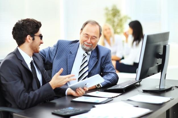 팀 작업의 배경에 회사의 재무 계획을 논의하는 두 사업가