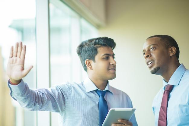 Two businessmen using transparent screen