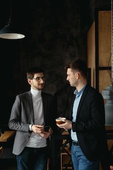 Due uomini d'affari con caffè, discutendo durante una pausa