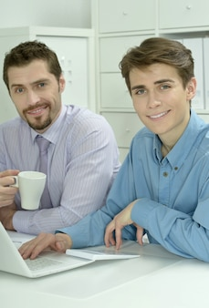 Two businessmen working on a laptop  at office