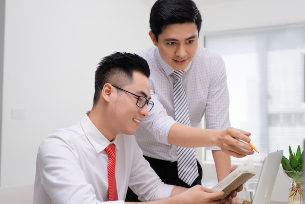 Два бизнесмена работают вместе с компьютером за офисным столом, один из них указывая на экран.