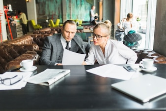 Two businesspeople analyzing document in caf�