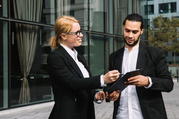 Two businesspeople discussing business project over clipboard at outdoors