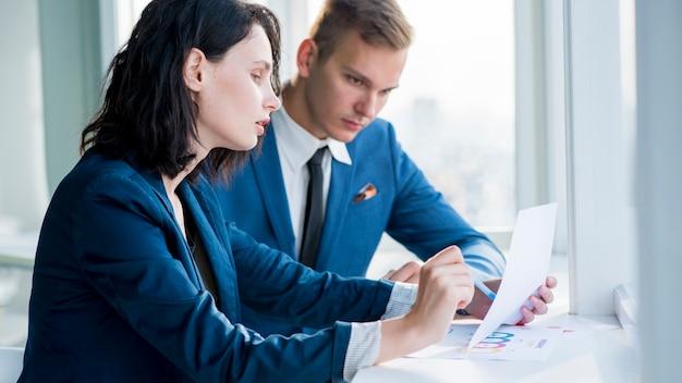 2つのビジネスマンは、職場でチャートを調べる