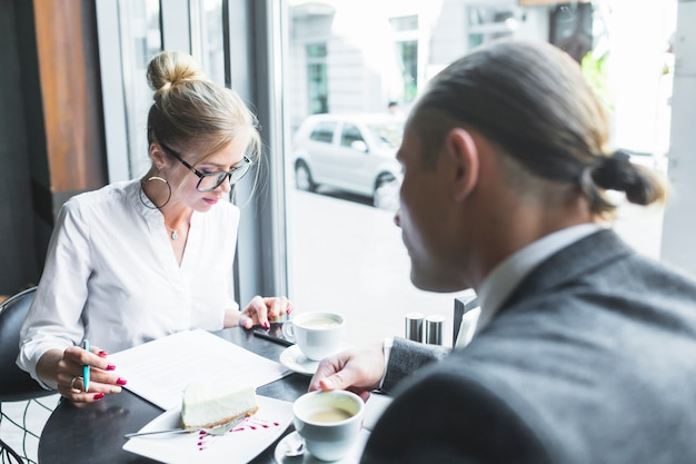 Two businesspeople examining document with cup of coffee on desk