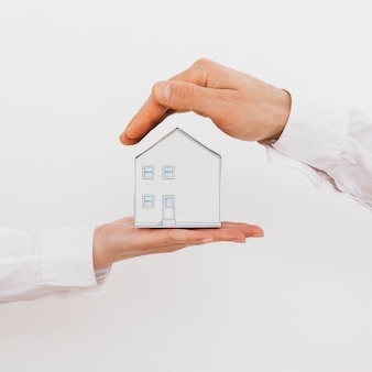 Two businesspeople hand's protecting miniature model house isolated on white background