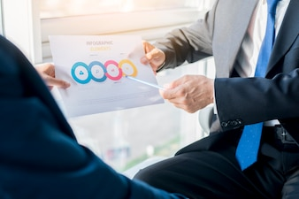 Two businesspeople holding infographic elements sheet