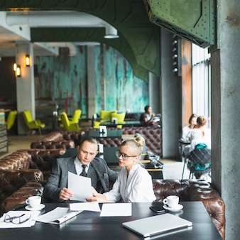 Two businesspeople looking at document in caf�