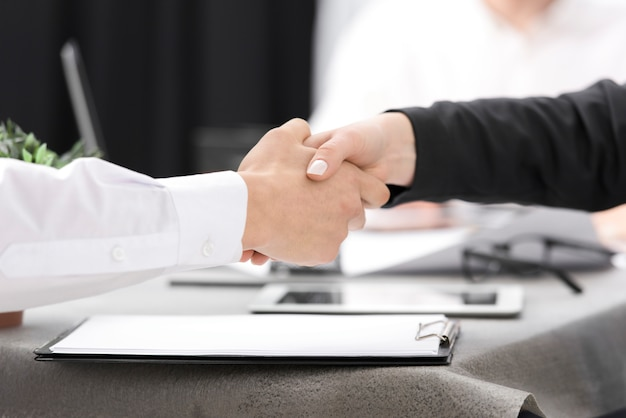 Two businesspeople shaking each other's hand over the clipboard on the desk