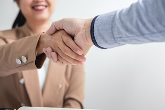 Two businesspeople shaking hands during a meeting to sign agreement